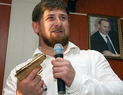 Ramzan Kadyrov poses with his golden gun in front of portrait of Vladimir Putin