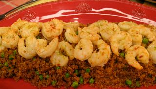 Quinoa and pan cooked shrimp on a red plate.