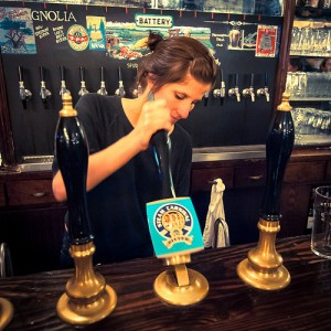 A young woman serves a pint of cask ale