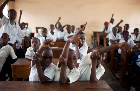 Students raise their hands to answer a class questions at the St. Louis Primary School in Kinshasa