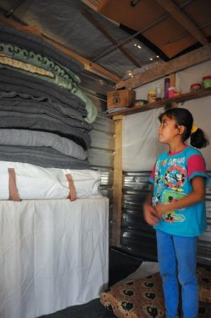 9-year-old Ayat looks at the blankets in her home — a tent in Za'atari Camp.