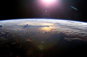 Photo de l'Océan pacifique vue de l'espace : les nuages sont en relief vu la levée du soleil.