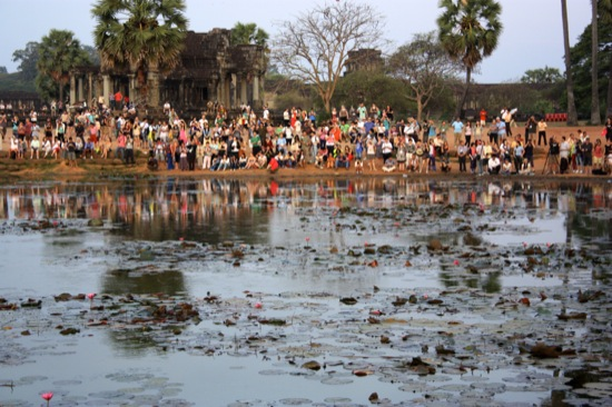 Crowd watches sunrise over Angkor Wat