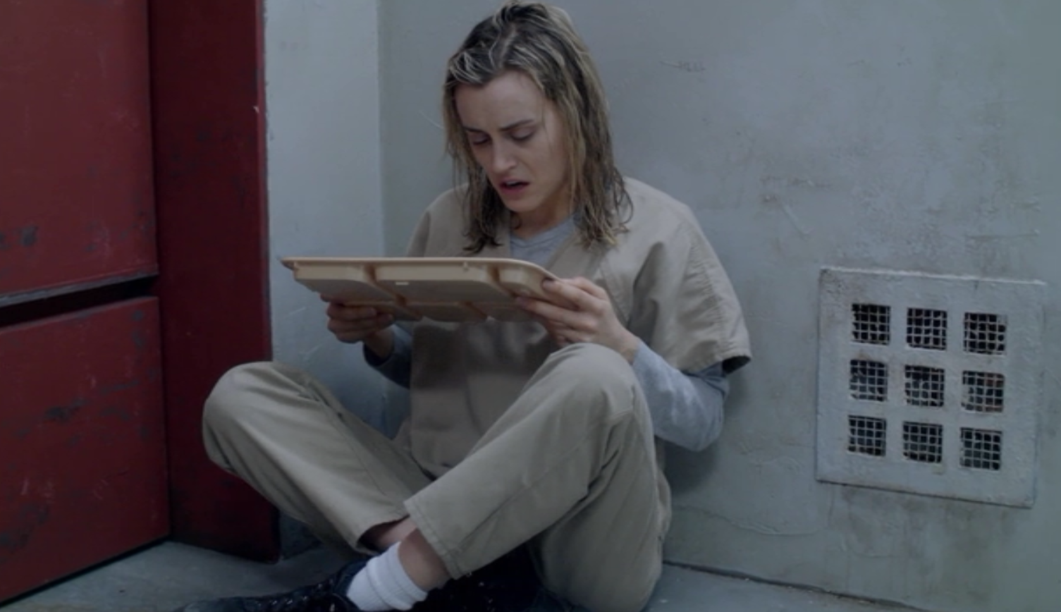 Piper grimacing in solitary confinement on the show