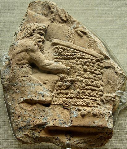 A terra cotta relief showing Satyrs, a Greek mythological creature, expressing the juice from trodden grapes in wicker mats