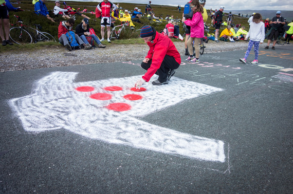 A man paints a king of the mountains shirt on the road in yorkshire