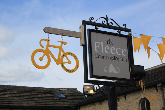 A yellow tour de France bicycle hangs from a pub sign