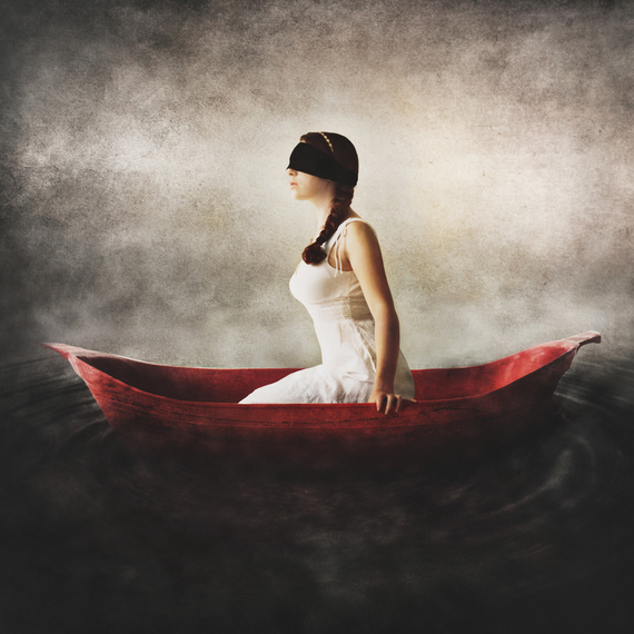 Surreal Fine Art by Jen Kiaba of a blindfolded woman in a white dress sitting in a red boat surrounded by darkness