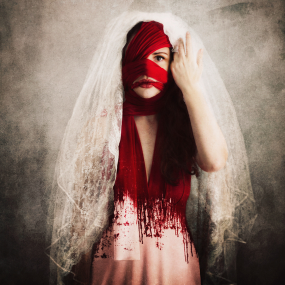Conceptual Fine Art by Jen Kiaba of a bride wrapped in bloodied bandages, lifting her veil to stare at the viewer