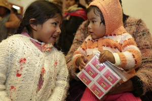 Two siblings receive Chispitas at a health centre in Bolivia.