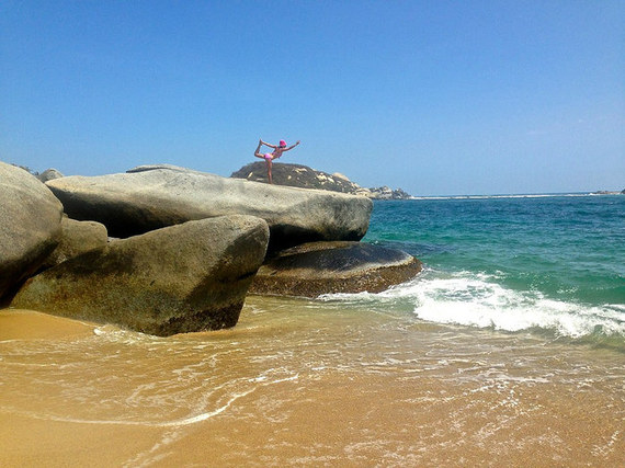 Bow pose on giant boulders Tayrona National Park Colombia