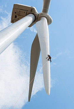 A worker inspects the blades of a wind turbine in Colorado. (Photo by Dennis Schroeder / NREL)