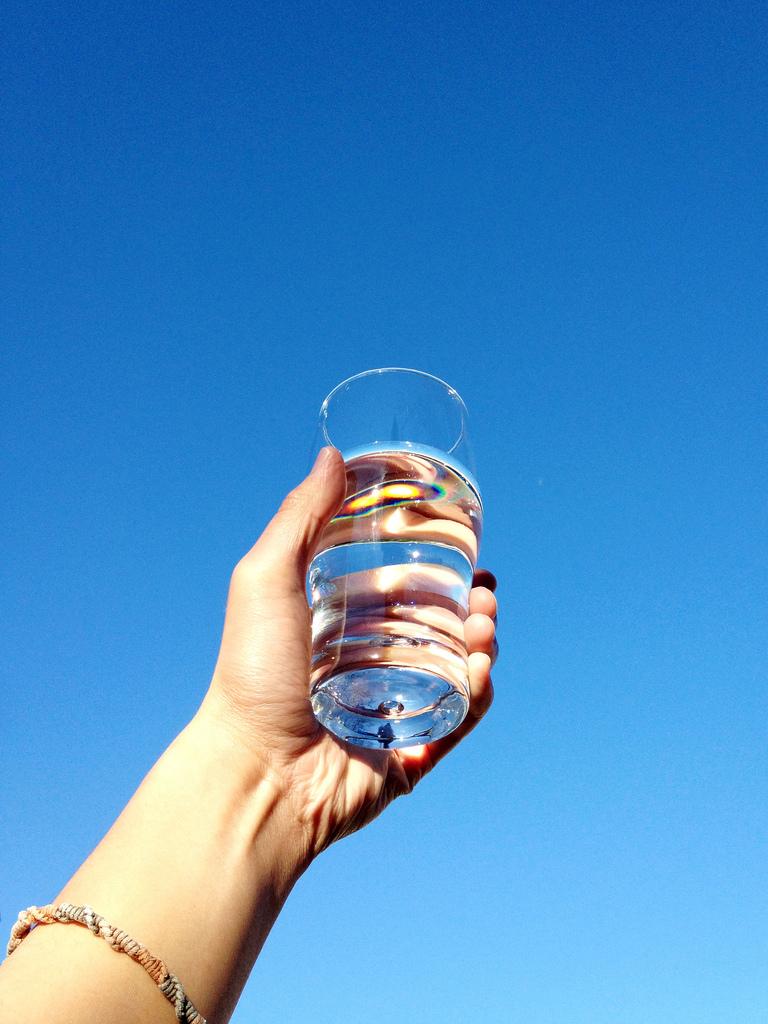 コップ一杯の水を飲む女性