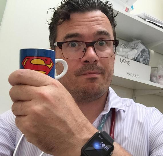 Dr Keith Grimes holding Superman coffee cup at work