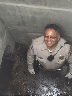 The officer as he rescues ducklings in the drainage tunnel. Photo from CHP