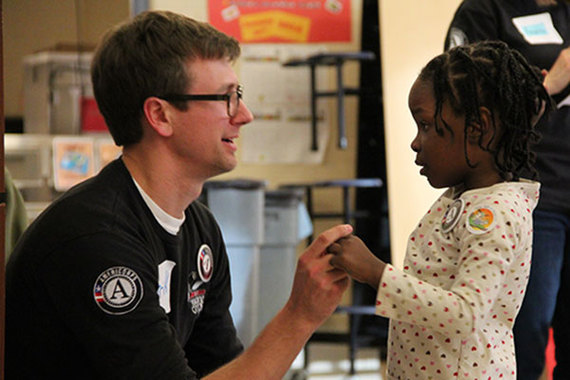 An AmeriCorps member talks with a child during the 2014 Martin Luther King Jr. Day of Service in Washington, D.C.