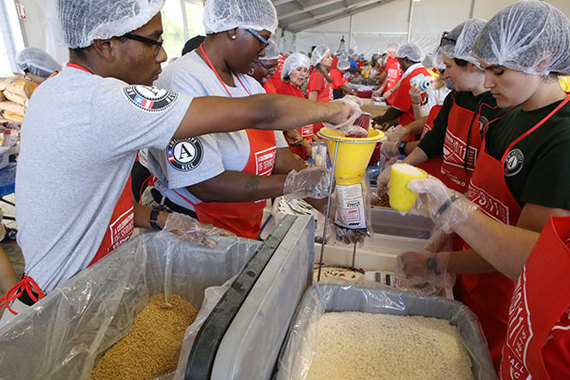 AmeriCorps members and other volunteers package meals at an AARP event on the National Mall in Washington, DC, on September 11, 2015.
