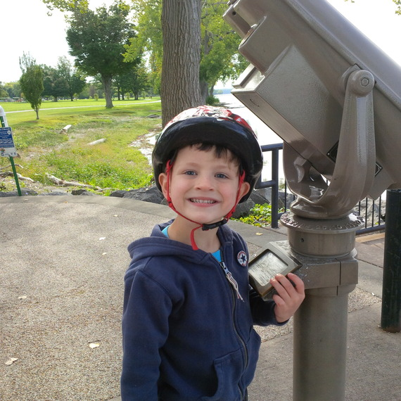 Kate's son wearing a helmet and smiling.