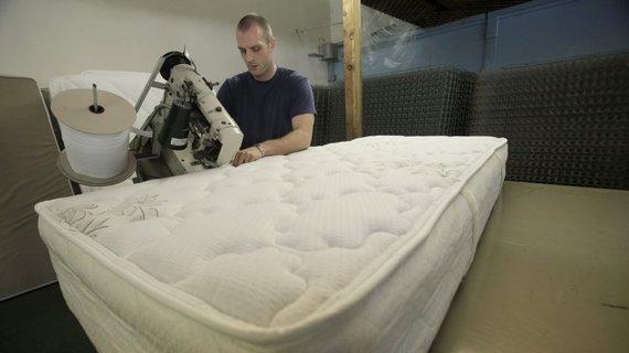 man sewing a mattress