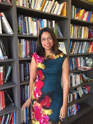 Fauzia Burke, author of Online Marketing for Busy Authors, standing in front of bookshelves