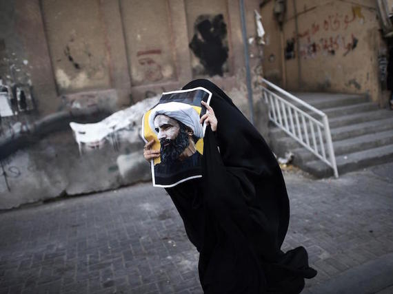 Bahraini woman holds poster of Ayatollah Nimr at protest AFP/Getty