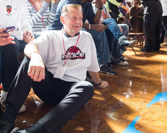 Father Dr. Michael Louis Pfleger, Senior Pastor of St. Sabina Church in Chicago, taking in the 2013 Peace League Basketball Tournament. Photo by Michael Yen