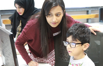 Faizah (centre) is studying Education at university and is one of the volunteers at the club (Photo Credit: Inventors Club Whitechapel)