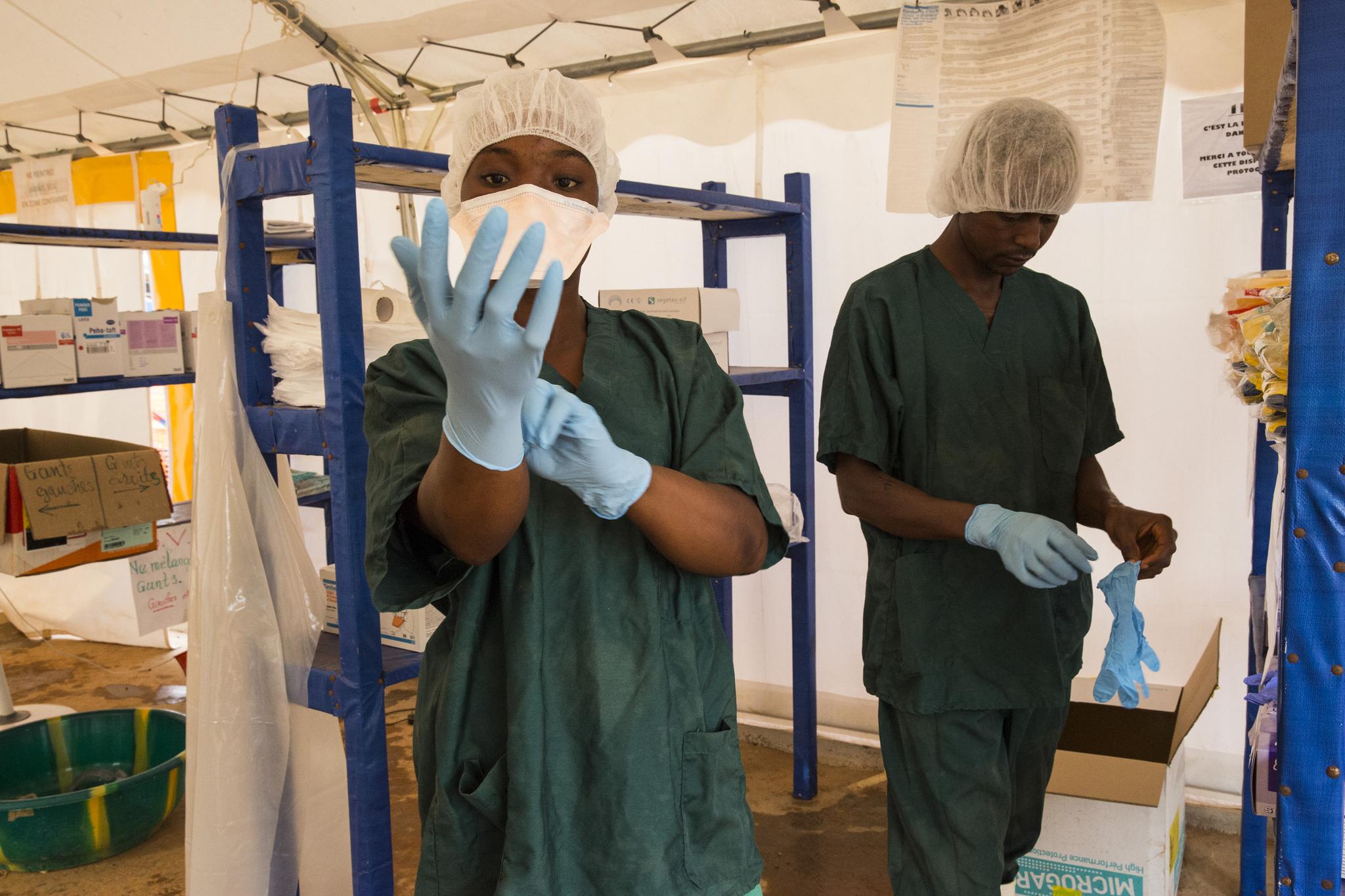 Zwei Helfer in Schutzkleidung im Behandlungszentrum für Ebola in Guinea - Foto: UN Photo/Martine Perret (CC BY-NC-ND 2.0)