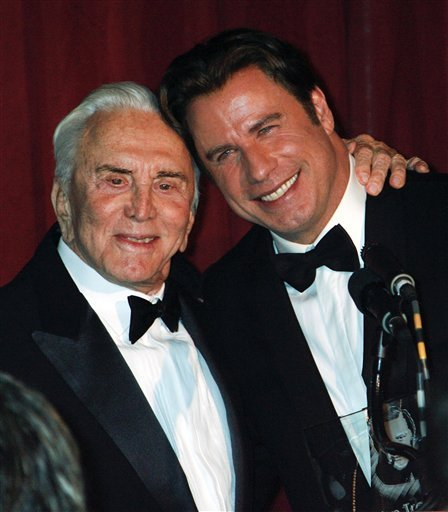 John Travolta Plants A Kiss On Kirk Douglas